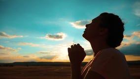 Girl praying. Girl folded her hands in prayer silhouette at sunset. slow motion video. Girl folded her hands in prayer
