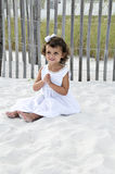 Girl with Praying Hands. Beautiful little girl dressed in white sitting on the sand with her hands in a prayer position Royalty Free Stock Image