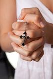 Girl praying hands with cross praying Stock Images