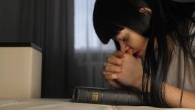 Girl praying indoors at bedtime on lifestyle bible. Religion concept evening prayer believer woman brunette hands on