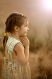 Girl prays in evening wheat field Royalty Free Stock Photo