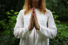 Girl prays with her hands. Girl wearing in white prays with her hands Stock Photography