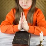 The girl prays at a table Royalty Free Stock Image
