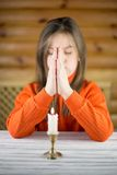 The girl prays at a table Royalty Free Stock Photos