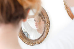 Girl preens in front of mirror Stock Images