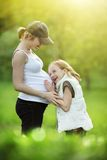 Girl with pregnant mother Stock Photography