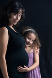 Girl with pregnant mum Royalty Free Stock Images