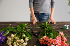 Girl prepare to make bouquet over gray background. Stock Photos