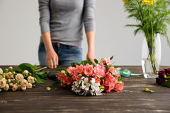 Girl prepare to make bouquet over gray background. Stock Photography