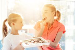 The girl prepared a surprise for her mother. Daughter gave mother a box of chocolates. Daughter feeds her mother with chocolate candies Stock Photography