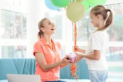 The girl prepared a surprise for her mother. Little girl prepared gift for mom. She holds balloons. Royalty Free Stock Image