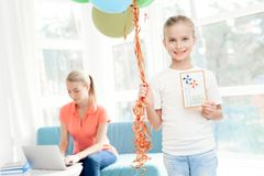 The girl prepared a surprise for her mother. Little girl prepared gift for mom. She holds balloons. Stock Images