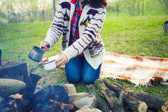 The girl prepares coffee in nature. Royalty Free Stock Images