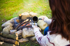 The girl prepares coffee in nature. Stock Photography