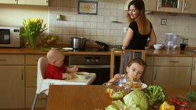 Girl prepares dinner in the kitchen at the same time looking for two children - a boy and a girl. Housewife at work