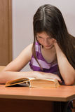 The girl prepares for examination. The girl sits at a school desk and reads the textbook Stock Photography