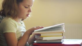 The girl prepares lessons, boredom reads books. He pushes a pile of books and takes the phone with joy. Internet