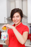 Girl prepares tea with lemon Royalty Free Stock Images