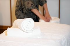 Maid cleaning at the spa. The girl prepares a workplace massage bed in the spa for the reception of clients. The maid is preparing a room for the spa salon Royalty Free Stock Photography