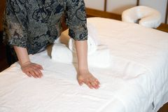 Maid cleaning at the spa. The girl prepares a workplace massage bed in the spa for the reception of clients. The maid is preparing a room for the spa salon Royalty Free Stock Image