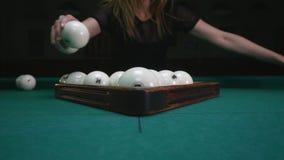 The girl preparing balls for play. Girl sets billiard balls and removes plastic triangle. Billiard balls in starting stock video