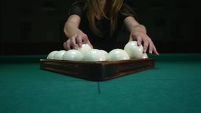 The girl preparing balls for play. Girl sets billiard balls and removes plastic triangle. Billiard balls in starting stock video footage