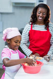 Girl preparing cake with mother. In kitchen Royalty Free Stock Photography