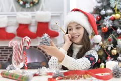 Girl preparing for  Christmas. Portrait of happy girl in Santa hat preparing for  Christmas sitting at the table and holding Christmas decoration Royalty Free Stock Photos