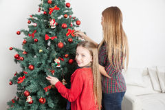 Girl preparing the christmas tree with her mom Stock Photography