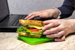 The girl is preparing for dinner at work, pulling out a sandwich, close-up laptop stock photos