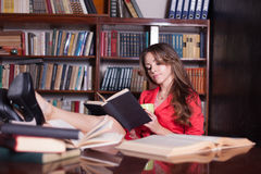 Girl is preparing for the exam in the library reads books Royalty Free Stock Photo