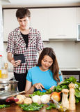 Girl preparing food while man looking at eBook Royalty Free Stock Photography