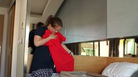 Girl preparing her suitcase for a travel, she is packing her clothes in bedroom. Happy girl preparing her suitcase for a travel, she is packing her clothes in stock video footage