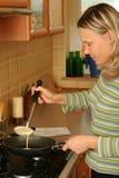 Girl preparing pancakes. Pretty smiling girl preparing pancakes at home stock image