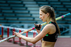 The girl is preparing for the pole vault Stock Photography
