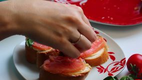 The girl is preparing sandwiches. Decorates the leaves of basil with pieces of salmon, lying on a loaf. Close-up on a white backgr. Ound stock video footage