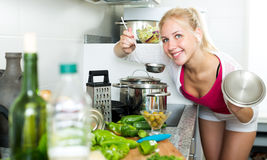 Girl preparing soup in cooking pot Stock Images