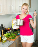 Girl preparing soup in cooking pot Royalty Free Stock Photos
