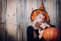 Girl preparing to cut a pumpkin. Witch in halloween hat posing outdoor. Portrait of young women in halloween costumes. Girl preparing to cut a pumpkin. Witch in royalty free stock photography