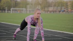 Girl preparing to run at the city stadium. stock video footage