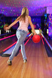 Girl preparing to throw of ball in bowling club. Back of girl wearing jeans and white T-shirt preparing to throw of ball in bowling club royalty free stock photos