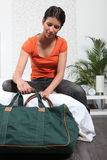 Girl preparing travel bag. Woman about to leave her house with baggage Royalty Free Stock Photo
