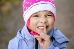 Girl-preschooler in blue jacket. Put finger to his lips Stock Image