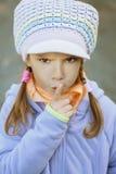 Girl-preschooler in blue jacket. Put finger to his lips Stock Photo