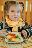 Girl-preschooler eats a tasty meal Stock Image
