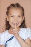 Girl-preschooler put finger to his. Happy girl-preschooler put finger to his lips Royalty Free Stock Images