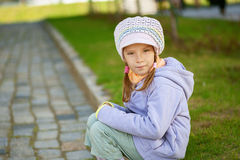 Girl-preschooler sitting on stone Stock Photography