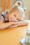 Girl-preschooler sitting at table Stock Images