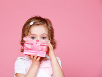 Girl with present. Portrait of a cute little girl hiding face behind pink present box Stock Image