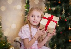 Girl with present box wondering at Christmas Stock Images